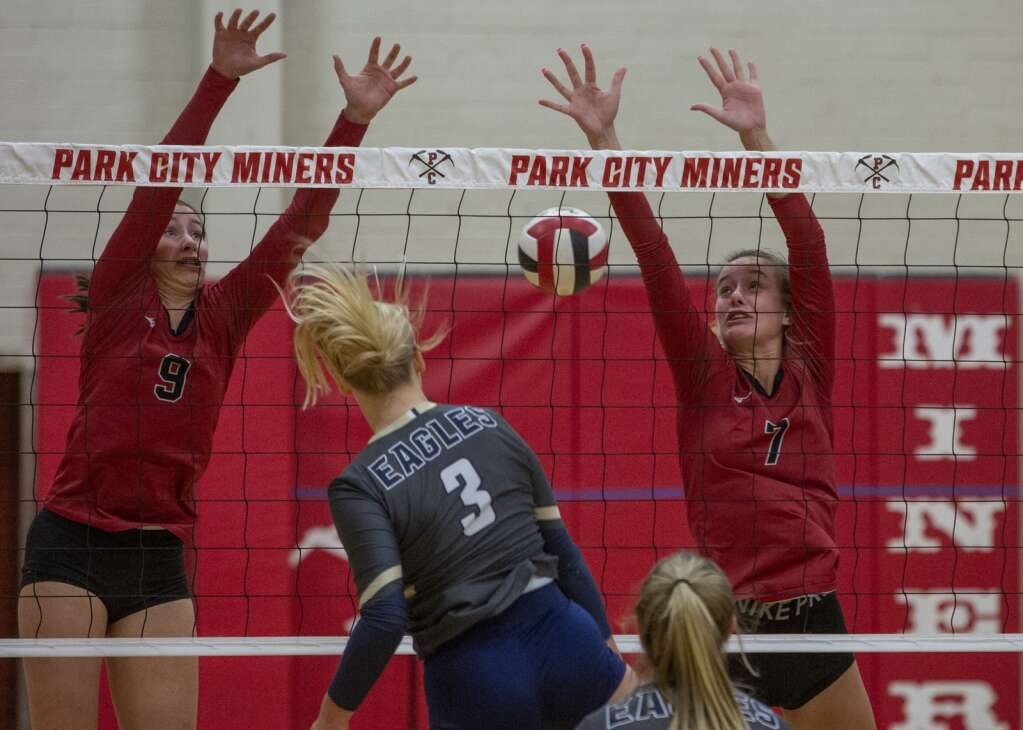 Park City High School junior Emma Cusimano (9) and senior Grace Crosby (7) jump up to the net to block a spike from Skyline High School's Kira Little (3) during their matchup Tuesday evening, Sept. 21, 2021. The Miners were swept 3-0 by the Eagles. (Tanzi Propst/Park Record)