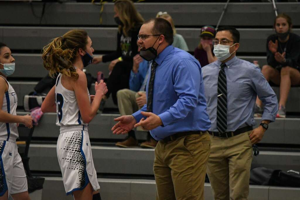 The Coal Ridge Titan girls basketball head coach Clyde Morgan cheers on his players as they return to the bench during Tuesday night's playoff game against the Ellicott Thunderhawks. |Chelsea Self / Post Independent