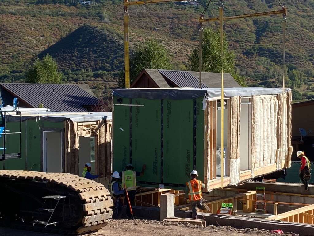 Construction workers help place a module into building 10 at Burlingame Ranch.