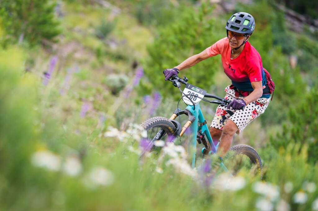 Melissa Trainer rides through a bounty of wildflowers on her way to winning the women's 45+ division at Wednesday's Soda Creek Scramble mountain bike race in Keystone.   Photo by John Hanson