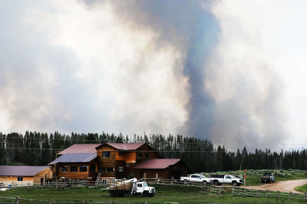 Smoke from the Muddy Slide Fire rises behind a home on Routt County Road 16, east of Yampa. (Photo by John F. Russell)