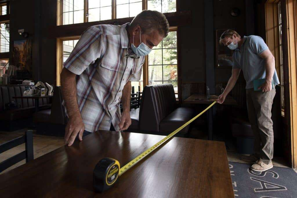 Tim Applegate, left, owner of Sauce on the Blue in Silverthorne, and Rob Baer use a tape measure to space tables 6 feet apart May 26. After more than a two-month closure, restaurants throughout Colorado were allowed to reopen at limited capacity May 27. | Photo by Jason Connolly / Summit Daily archives