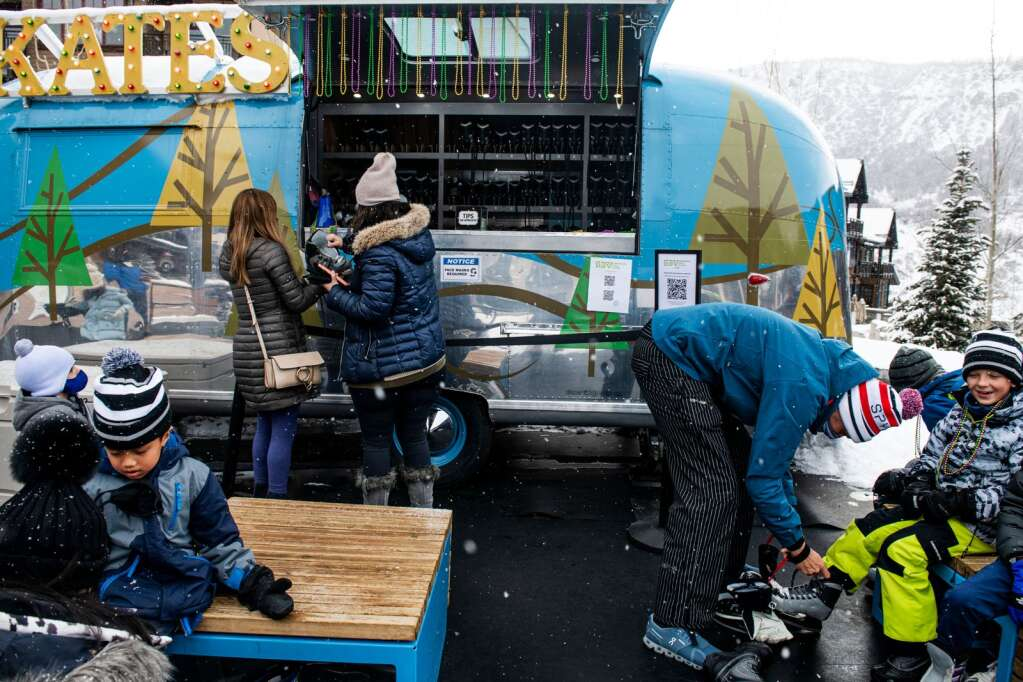 Ice skaters get Mardi Gras beads at the ice skating rink in Snowmass Base Village on Tuesday, Feb. 16, 2021. (Kelsey Brunner/The Aspen Times)