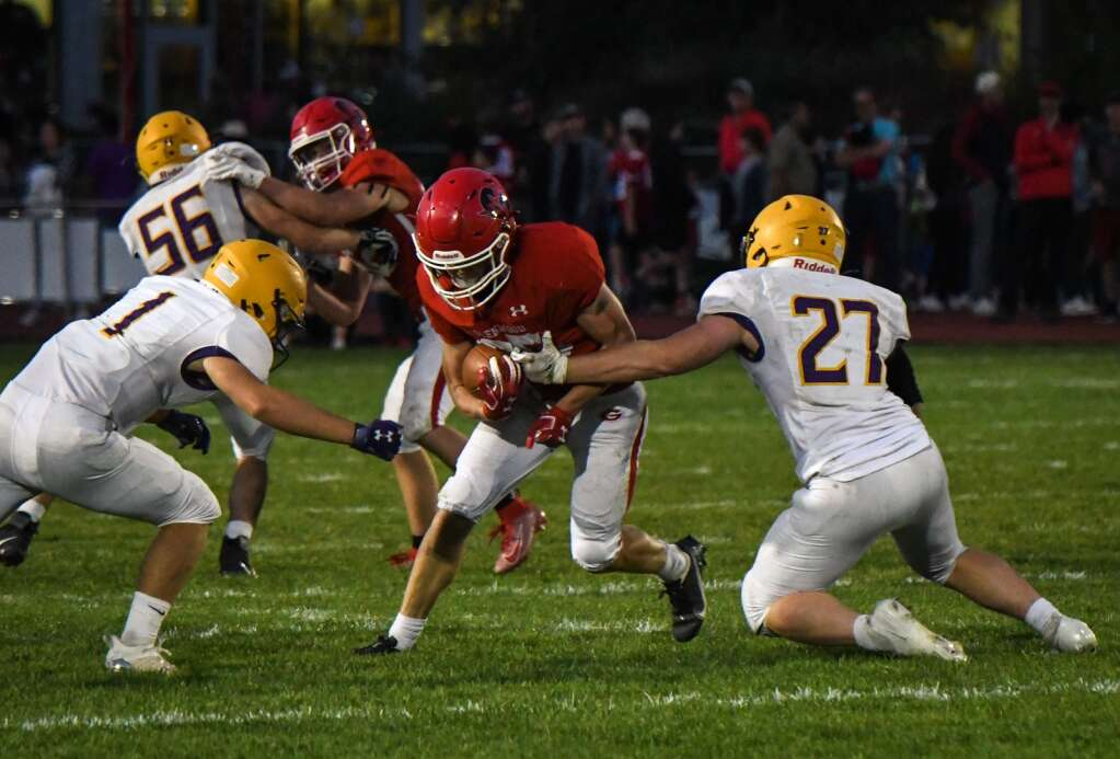 Glenwood Springs Demon Reece Mcmillan tries to squeeze through the Basalt Longhorn defense during Friday night's game at Stubler Memorial Field. |Chelsea Self / Post Independent
