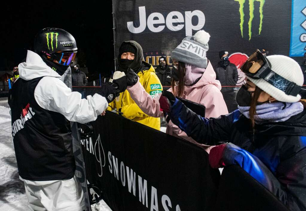 Japanese snowboarder Yuto Totsuka, left, fist bumps his teammates and coach before taking his last run during the men's superpipe finals at X Games Aspen on Sunday, Jan. 31, 2021. (Kelsey Brunner/The Aspen Times)