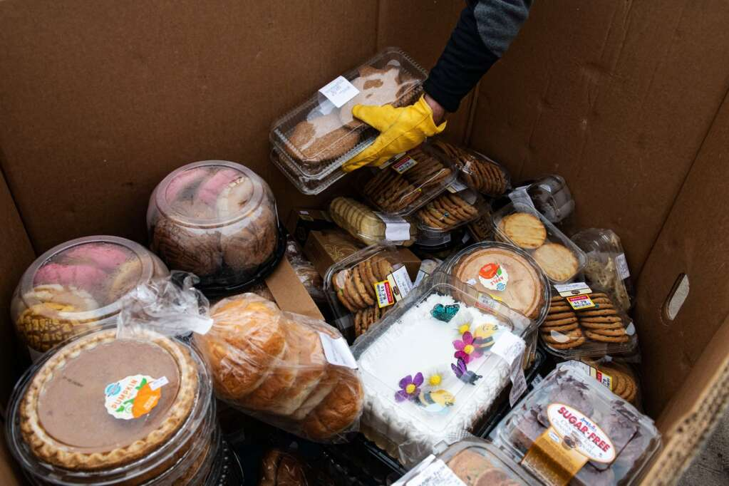 Food Bank of the Rockies' Ted McCune stacks food in a box delivered from Harvest for Hunger to be donated through a food drive in Crown Mountain Park in El Jebel on Tuesday, March 23, 2021. (Kelsey Brunner/The Aspen Times)