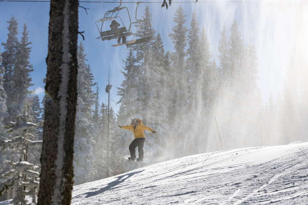 A snowboarder jumps off a mound of freshly made snow under the Gents Ridge Lift on Aspen Mountains opening day on Wednesday, Nov. 25, 2020. (Kelsey Brunner/The Aspen Times)
