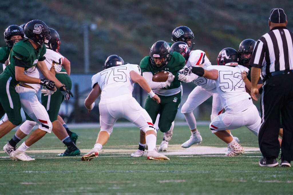 Summit High School senior running back Alex Sanchez plows his way through the Aspen Skiers defense early in the first half of the Tigers' win over Aspen Friday, Sept. 10, at Tiger Stadium in Breckenridge. | John Hanson/For the Summit Daily News