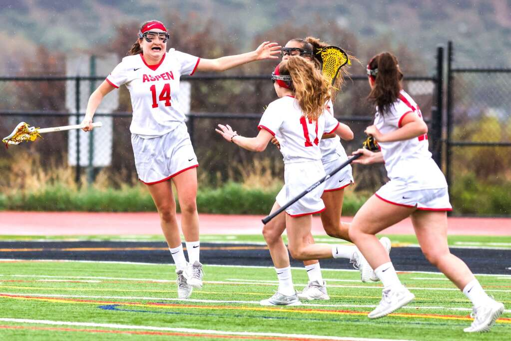 Aspen High School junior Mia Seltzer, left wearing No. 14, celebrates her game-tying goal late in the girls lacrosse game against Roaring Fork on Monday, May 17, 2021, on the AHS turf. Photo by Austin Colbert/The Aspen Times.