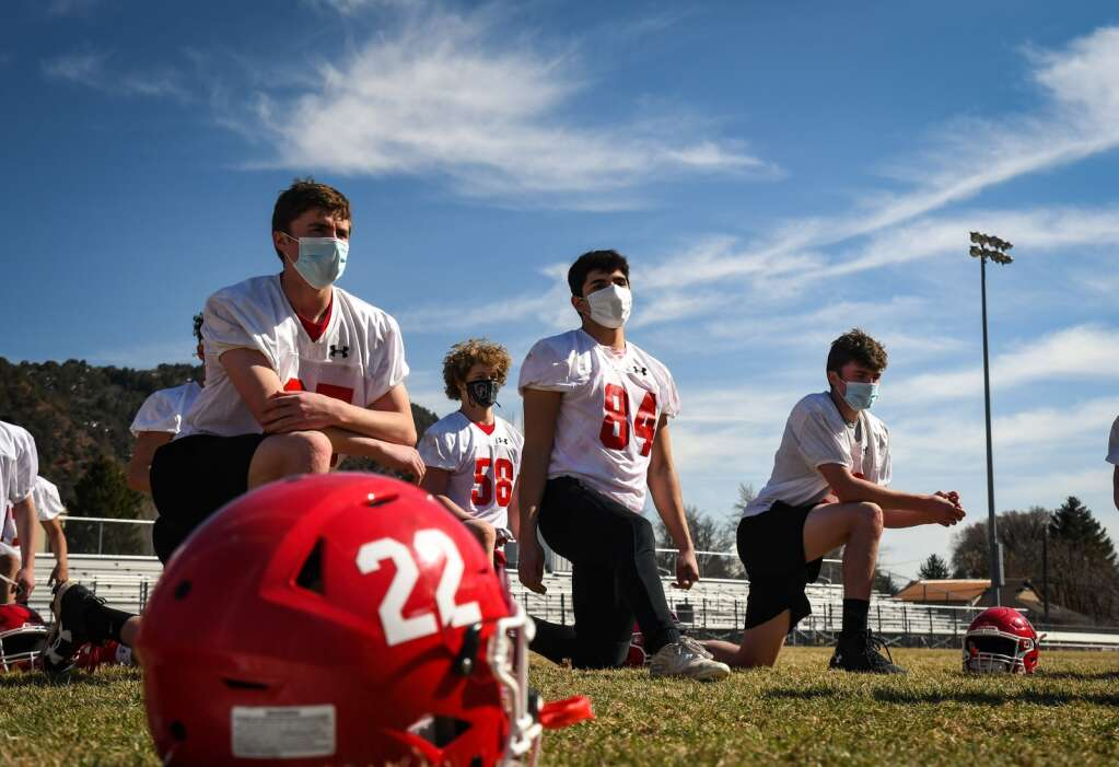 The Glenwood Springs High School Demon football team stretch and warm-up before practice at the school on Thursday. |Chelsea Self / Post Independent