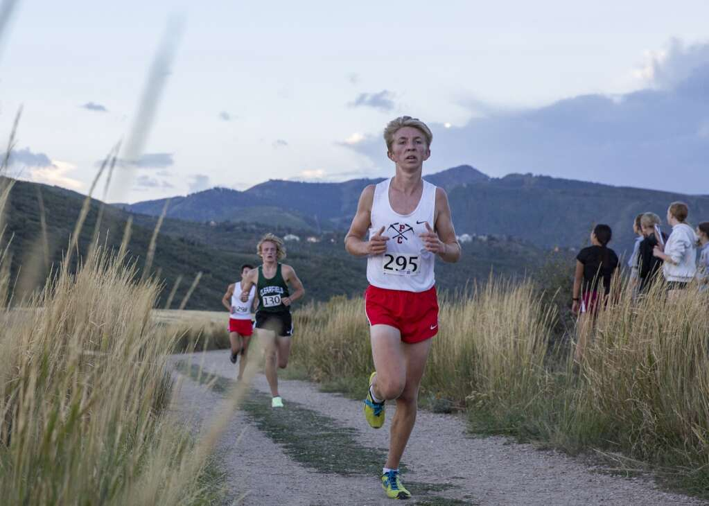 A Park City High School varsity runner picks up the pace as he approaches the final stretch of the course during the Park City High School invitational cross country meet in Round Valley Friday evening, Sept. 10, 2021. (Tanzi Propst/Park Record)