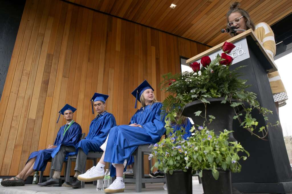 Saxon Netzel, center, listens as teacher Amanda Wilson speaks during the Snowy Peaks High School graduation Wednesday, May 26, at the Silverthorne Performing Arts Center in Silverthorne.   Photo by Jason Connolly / Jason Connolly Photography