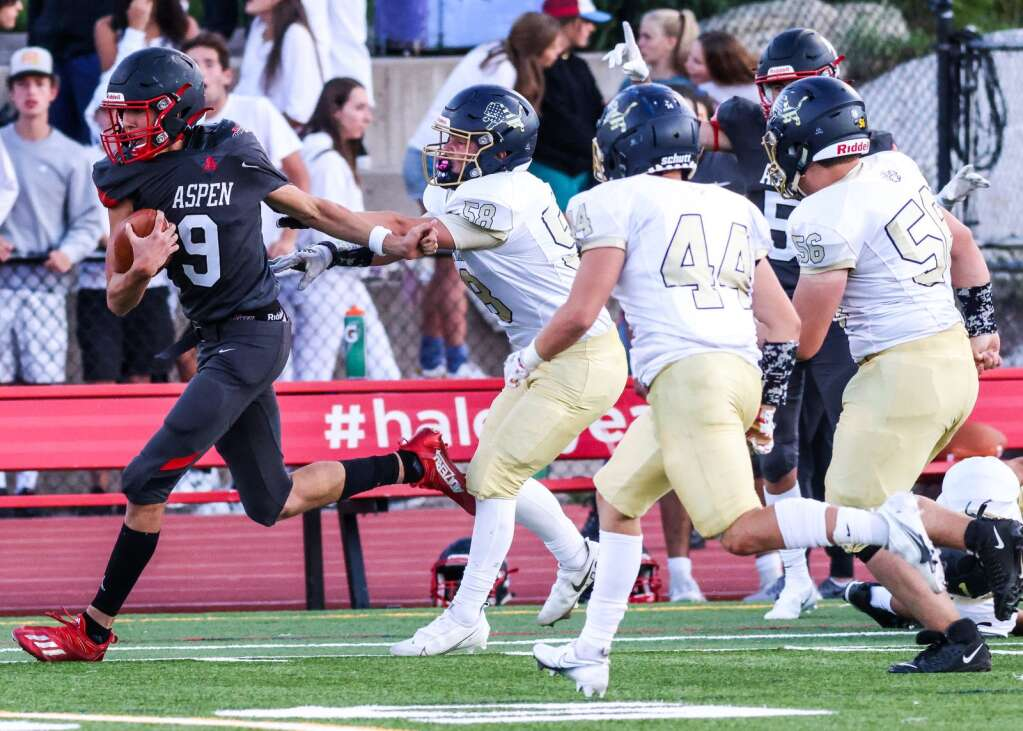 Aspen High School's Porter Lee, left, races down the sideline as the football team hosts Colorado Springs Christian on Friday, Aug. 27, 2021, on the AHS turf. | Photo by Austin Colbert/The Aspen Times
