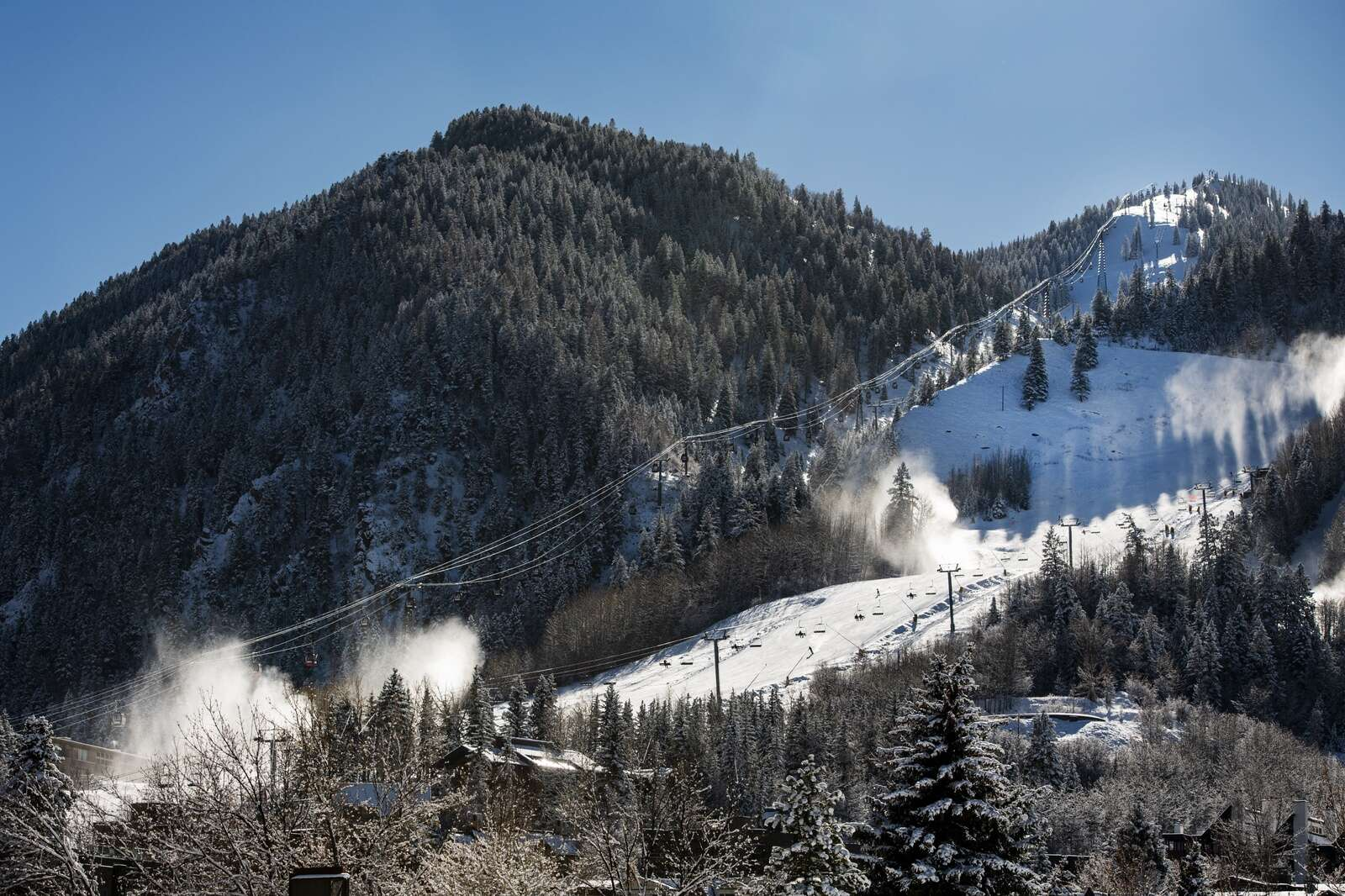 Snowmakers blow snow onto the Little Nell run as people make their way down Aspen Mountain on opening day on Wednesday, Nov. 25, 2020. (Kelsey Brunner/The Aspen Times)