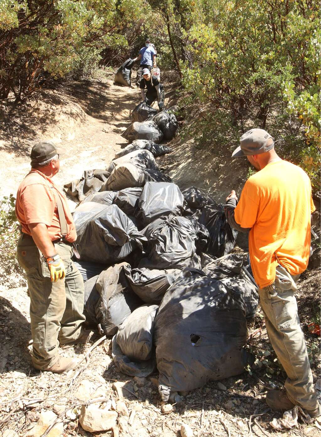 Bag after bag full of refuse pulled from the Sugarloaf Mountain homeless encampments is rolled down the trail until they can be put into garbage dumpsters July 1. | Photo: Elias Funez