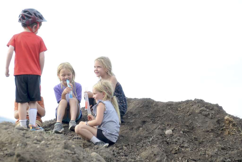 Children climb a dirt pile near the Howelsen Hill Ice Arena at the Town Challenge Emerald Endurance race on Wednesday evening. (Photo by Shelby Reardon)