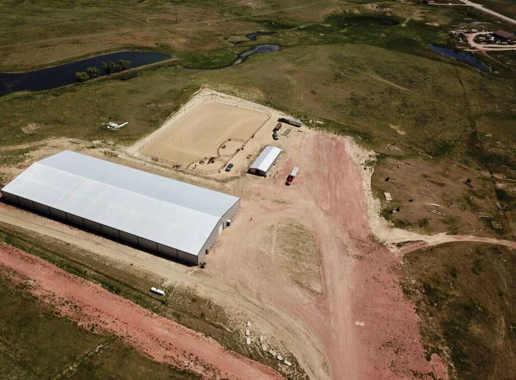 An overhead view of the Kluz Performance Horses facility, which includes a 120' x 300' heated indoor arena and a 200' x 300' outdoor arena. The facility is located near Gillette, Wyo.