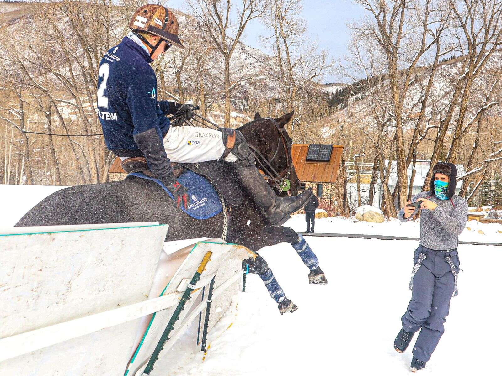 California's Jason Crowder, a professional polo player, and his horse crash through the fence as a spectator looks to get out of the way during the final of the World Snow Polo Championship on Sunday, Dec. 20, 2020, at Rio Grande Park in Aspen. Crowder, playing for Royal Salute, the horse and the spectator were unharmed, although there was a short delay to fix the wall. Royal Salute lost to World Polo League in the championship game, 11-10 in a shootout. (Photo by Austin Colbert/The Aspen Times)