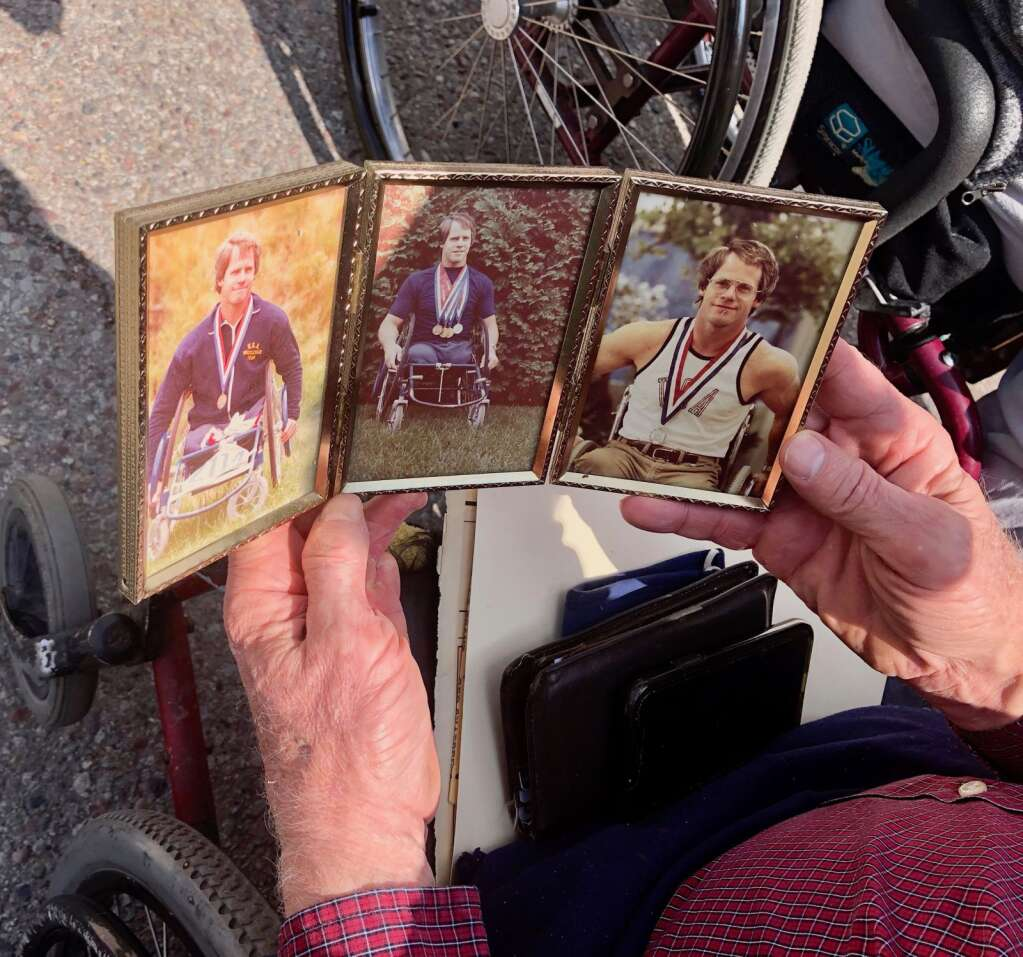 Jim Finch holds a display of photos showing him after winning medals at the 1980 Summer Paralympics. | Scott Condon/The Aspen Times