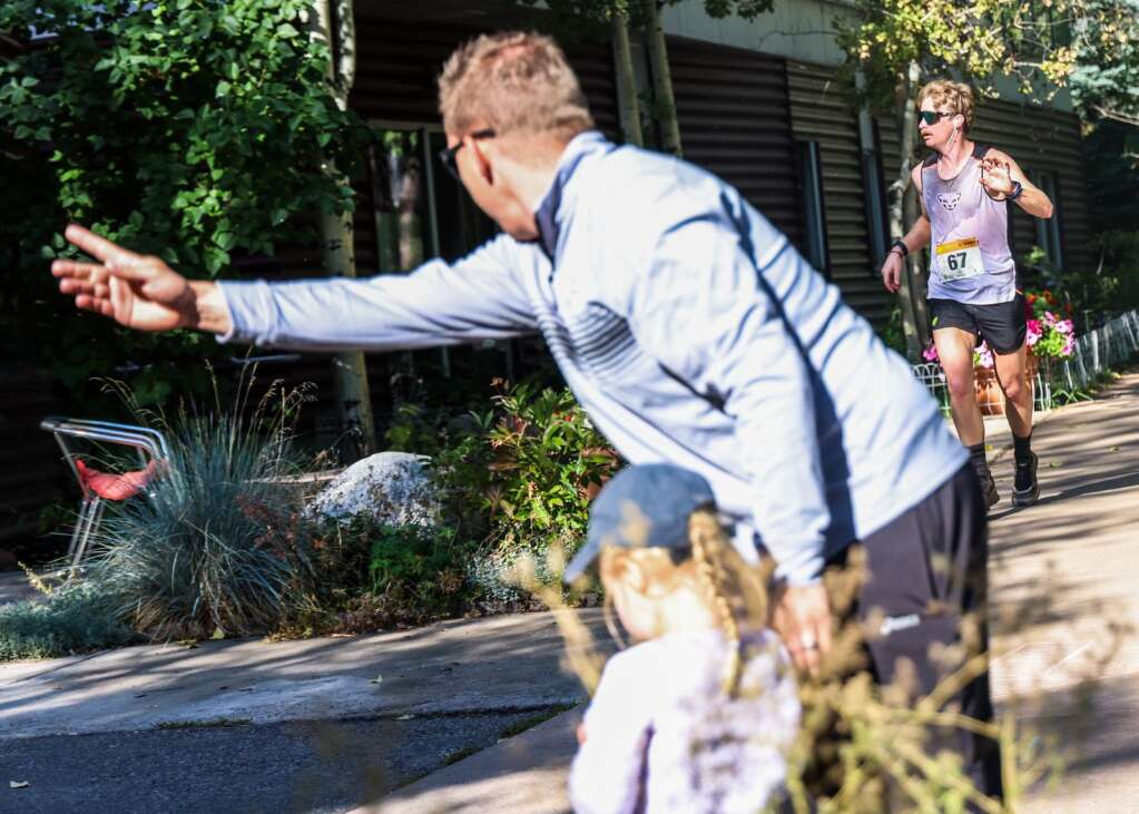 Garrett Seddon helps direct runner TJ David of Carbondale during the Golden Leaf half marathon on Saturday, Sept. 18, 2021, in Aspen. David finished fifth overall. Photo by Austin Colbert/The Aspen Times.