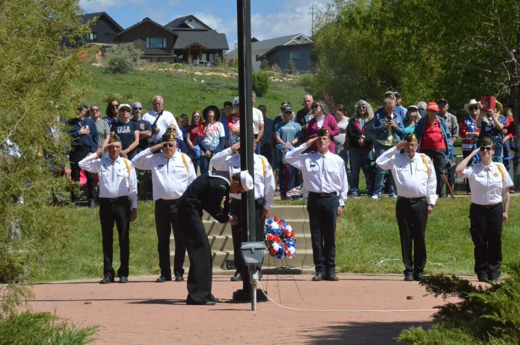 Local veterans salute as the U.S Flag is lowered to half staff during a Memorial Day ceremony at Steamboat Springs Cemetery on Monday. (Photo by Dylan Anderson)