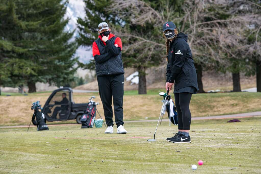 Aspen High School's athletic director and girls golf team assistant coach Martha Richards assists junior Maya Shindel with her putting drill during practice at the Aspen Golf Club on Wednesday, April 21, 2021. (Kelsey Brunner/The Aspen Times)