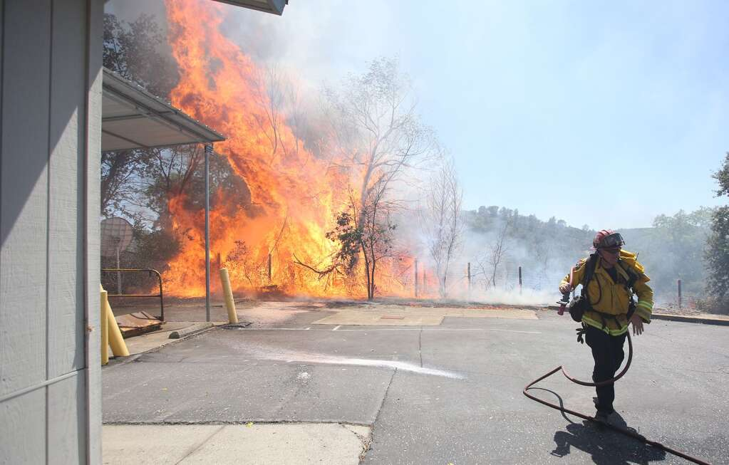A firefighter works swiftly to protect the Smartsville Post Office and other structures threatened during the Smartsville Fire which burned approximately 12 acres July 9.