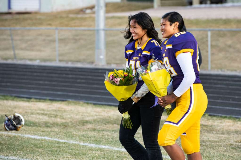 Twins Katie, left, and Chandra Bohannan walk to their parents as they're honored on senior night with the rest of their teammates at Basalt High School on Friday, April 9, 2021. (Kelsey Brunner/The Aspen Times)