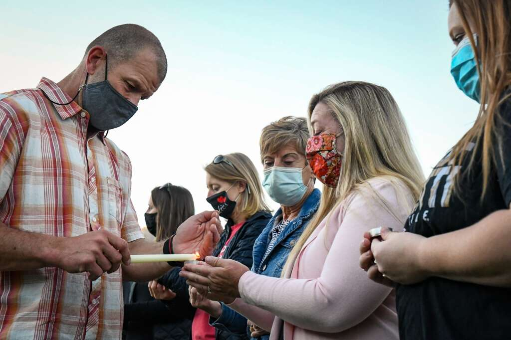 Glenwood Springs High School Vice Principal Pat Engle lights candles for people before the start of the candle light vigil for late Jim Benson who passed away last Saturday.  Chelsea Self / Post Independent