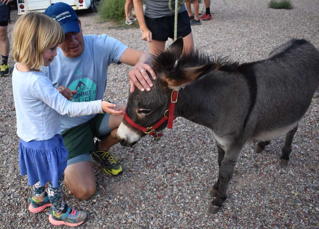 Independence Run & Hike owner Brion After and daughter Arbaney with Dylan the miniature donkey. | Tami Stroud/Courtesy photo