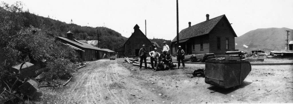 Six men sitting on and around a pile of logs on the grounds of the lower Durant Mine. A large ore car sits in the foreground to the right. There is a pile of twisted scrap metal to the far left and Smuggler Mountain can be seen in the back ground. | Aspen Historical Society