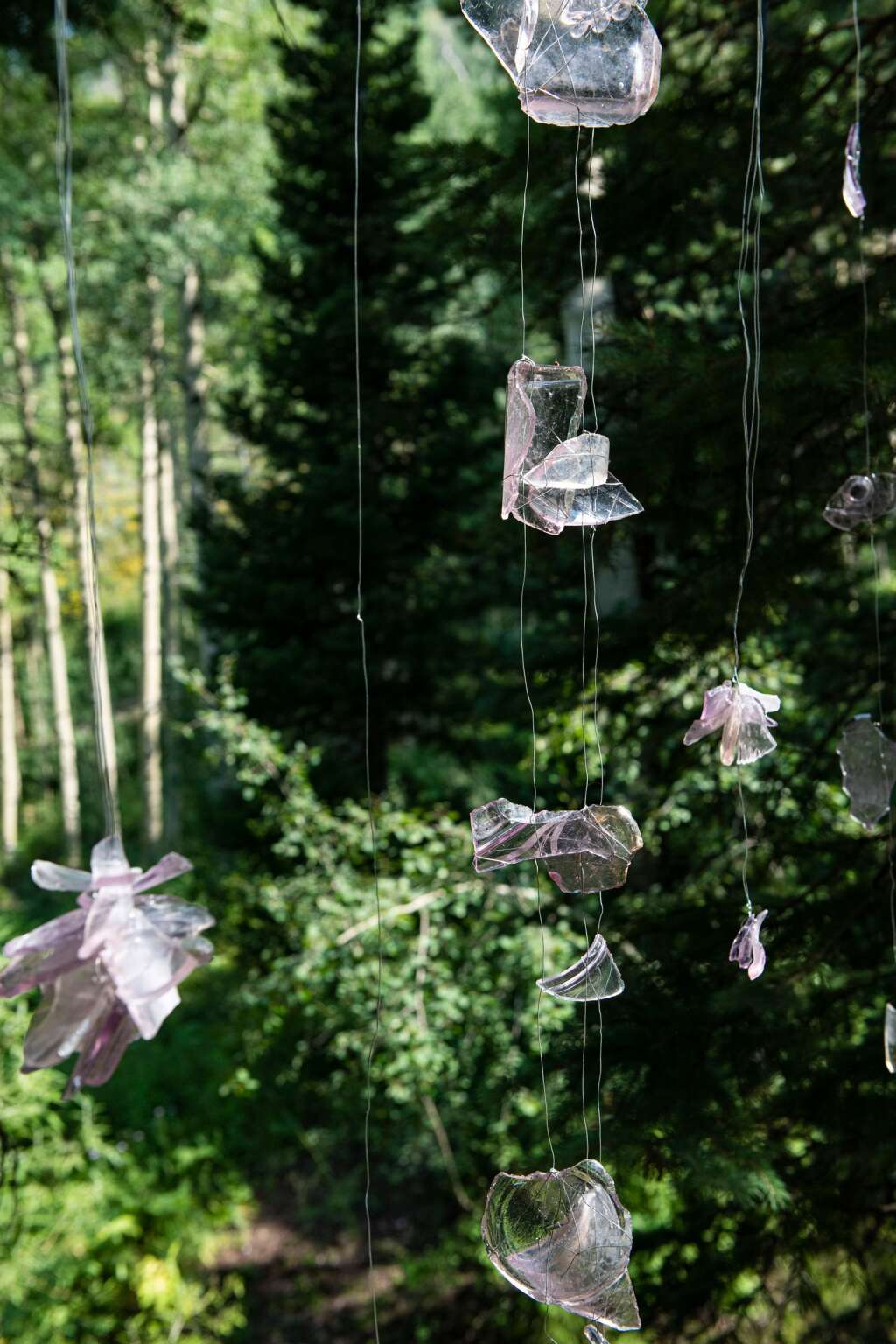 """Found glass shards hang in the """"Earthly Palace Forest Shrine"""" created by local artist Lara Whitley for the """"Aspen Space Station"""" on the backside of Aspen Mountain.  (Kelsey Brunner/The Aspen Times)"""