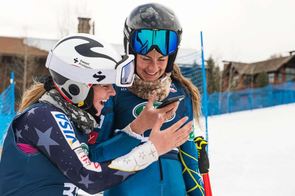 American alpine skiers Paige Doyle, left, and Resi Stiegler check their scores at the bottom of Aspen Highlands after the Women's Giant Slalom National Championships course on Thursday, April 15, 2021. (Kelsey Brunner/The Aspen Times)
