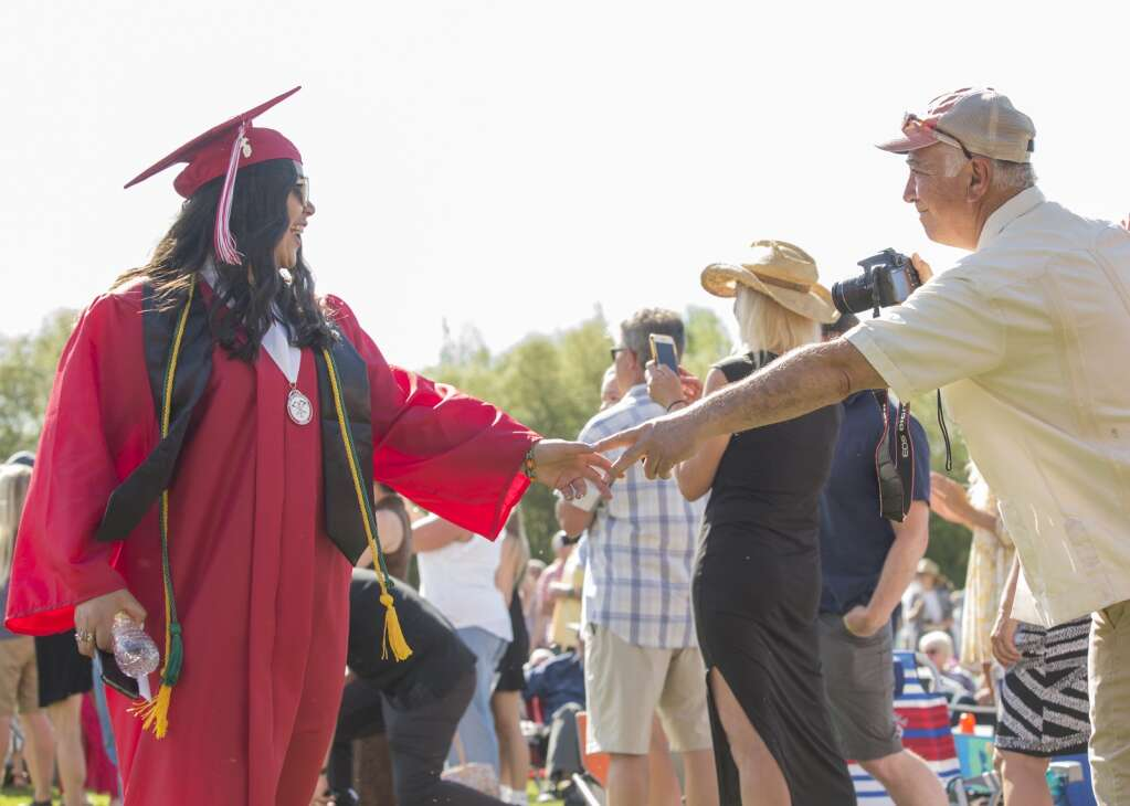 A Park City High School graduate reaches out to touch hands with her father as she and her classmates process into the bleachers on the North 40 playing fields Thursday evening, June 3, 2021. More than 1,000 people attended the ceremony. (Tanzi Propst/Park Record)