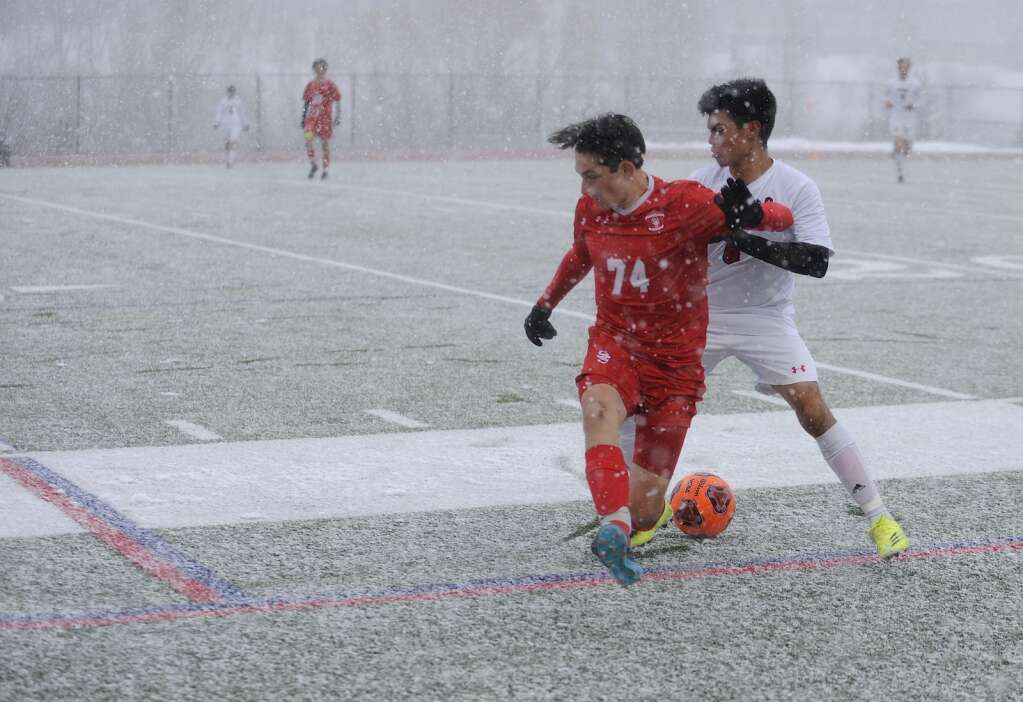 Steamboat Springs junior Liam Catterson keeps Glenwood Springs senior Richie Flores at bay during a snowy game on Thursday evening. (Photo by Shelby Reardon)