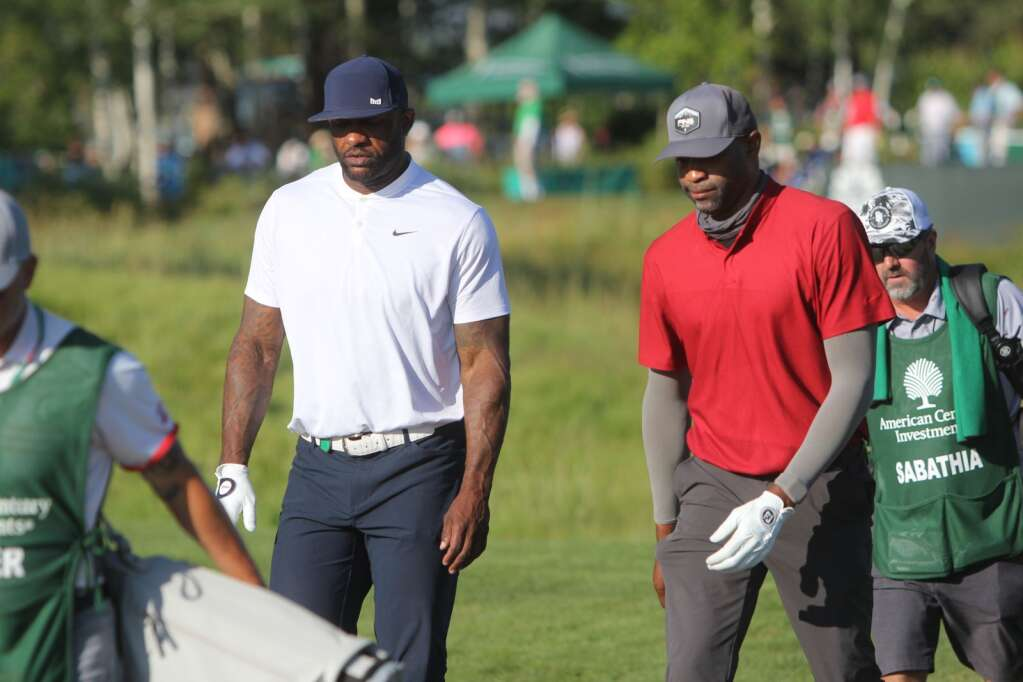 Cc Sabathia and Vince Carter (right) head to their opening tee shots.
