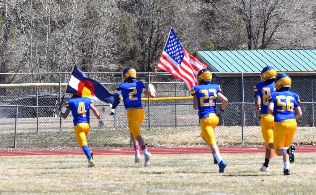 Rams players carry the American and Colorado flags onto the field before the start of the team's first varsity home game since 2017 Saturday afternoon in Carbondale.