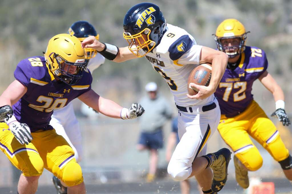 Rifle quarterback Gavin Peterson runs with the ball against Basalt on Saturday, April 3, 2021, on the BHS field. The Longhorns won, 38-7. Photo by Austin Colbert/The Aspen Times.