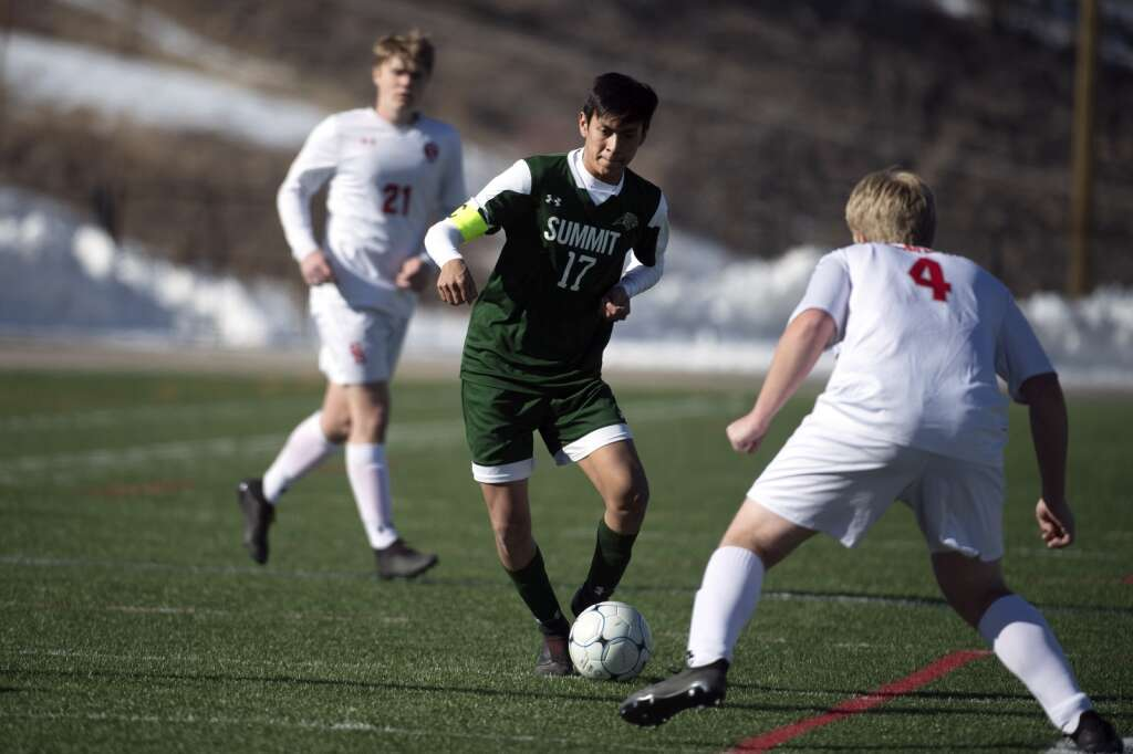 Summit High Tiger Alex Casillas controls the ball against a Steamboat Springs defender during the home opener of the boys varsity soccer season at Climax Molybdenum Field at Tiger Stadium on Thursday, March 18, 2021. The Tigers lost to the Sailors 3-0. | Photo by Jason Connolly / Jason Connolly Photography