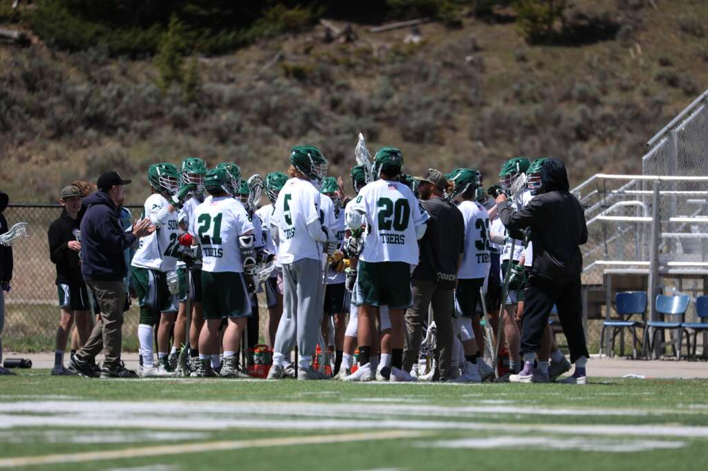 The Summit High School varsity boys lacrosse team huddles during their 11-8 loss to Battle Mountain on Saturday at Tiger Stadium in Breckenridge. | Photo by Ashley Low / Ashley Low Photography