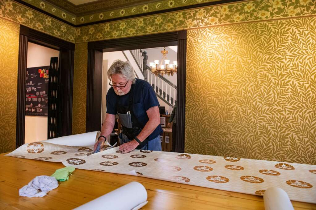 Charlie Hopkins cuts a strip of wallpaper to be applied to the walls of the Aspen Historical Society's victorian Wheeler-Stallard Museum on W. Bleeker St. in Aspen on Wednesday, May 12, 2021. (Kelsey Brunner/The Aspen Times)