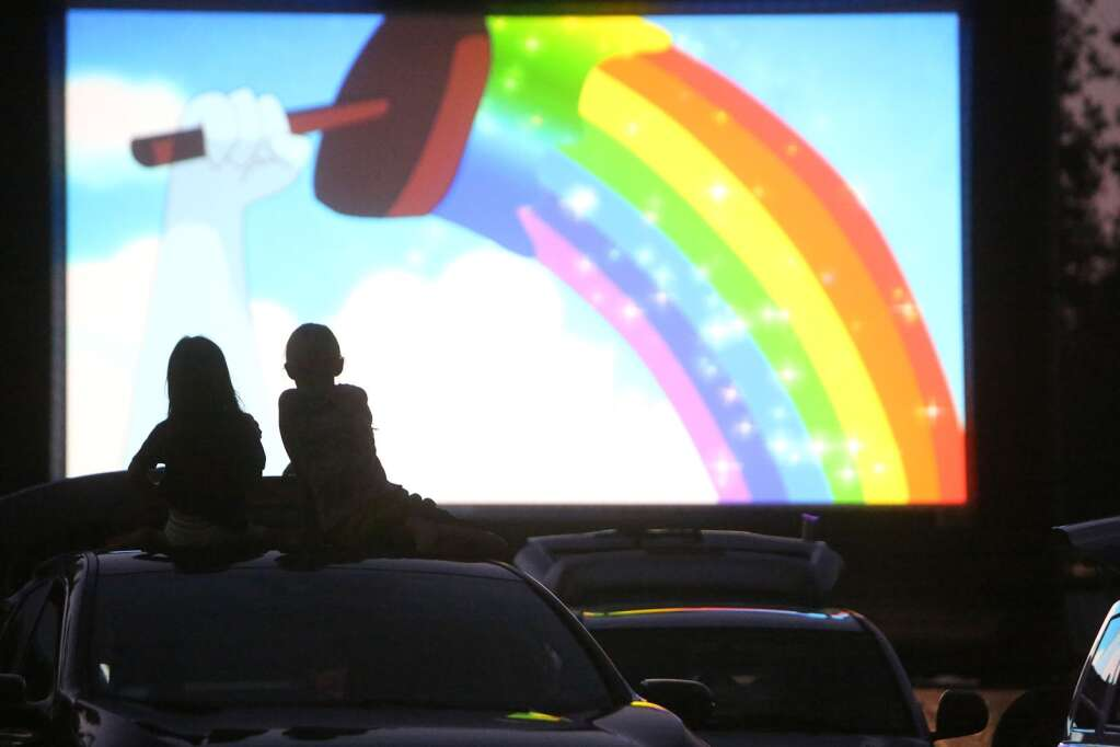 A pair of drive-in movie goers take in Tuesday night's family and children's film shorts atop a vehicle at the Nevada County Fairgrounds Sept. 2. | Photo: Elias Funez