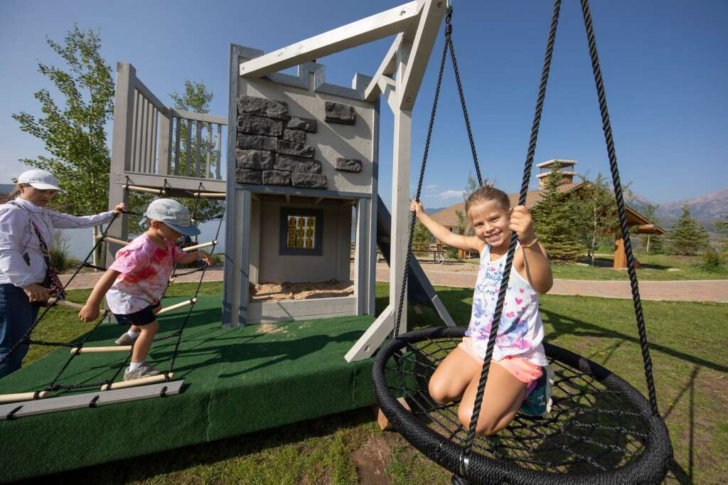 Children enjoy the Playhouse Project creations at the Marina Park in Dillon on Friday, Aug. 6. Each of the three playhouses will be auctioned off to raise money for Summit Habitat for Humanity.   Photo by Tripp Fay / Tripp Fay Photography.