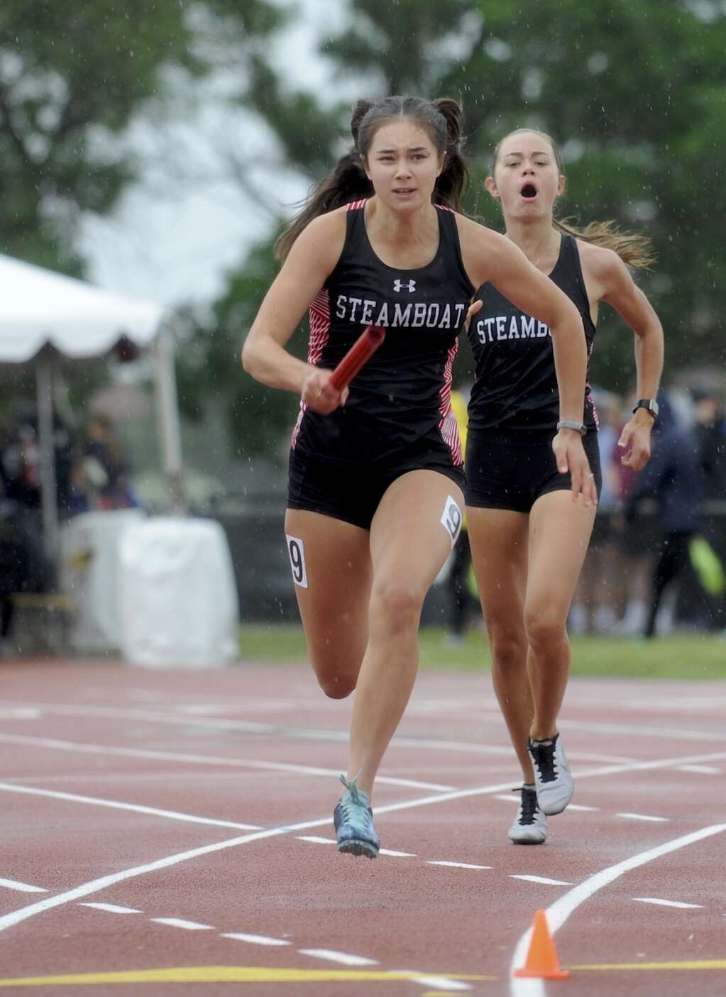 Steamboat Springs senior Aliyah Reimer takes off as the anchor leg of the girls 4x100 as junior Kelsey Hamilton yells encouragements at the CHSAA State Track and Field Championships at JeffCo Stadium on Saturday. (Photo by Shelby Reardon)