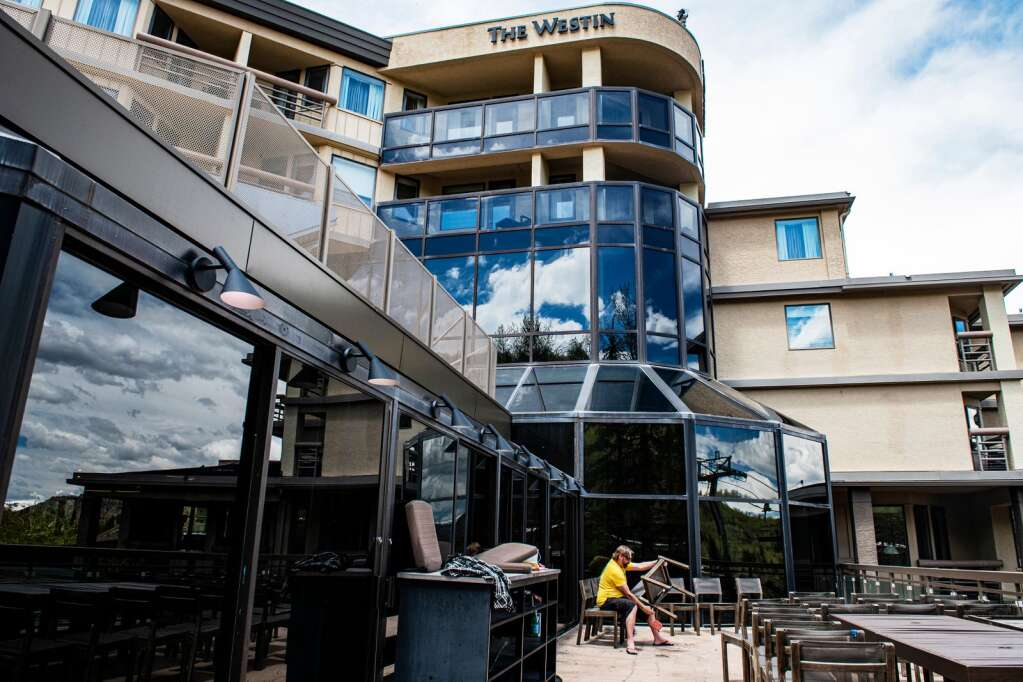 Josh Jones sands chairs on the back patio of The Westin in Snowmass Village on Tuesday, May 12, 2020. (Kelsey Brunner/The Aspen Times)