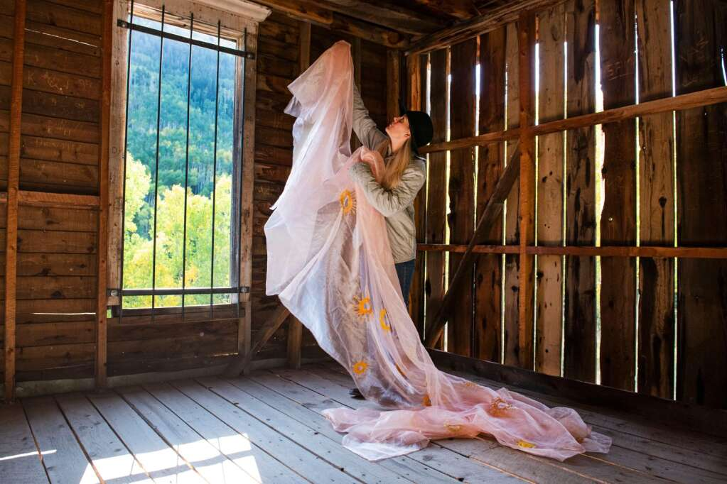 Denver-based artist Kaitlyn Tucek holds up a fabric piece for her installation in a building in the Ashcroft Ghost Town outside of Aspen as part of her two-day exhibition 'The Lilac Hour' outside of Aspen on Friday, Sept. 17, 2021. (Kelsey Brunner/The Aspen Times)