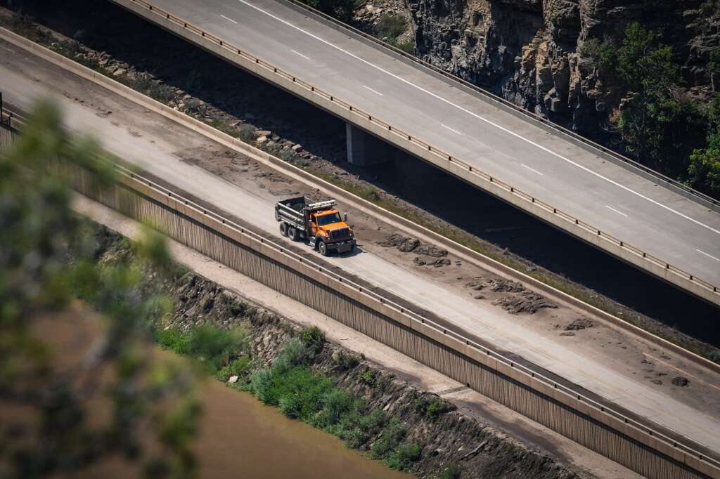 A CDOT dump truck heads east in Glenwood Canyon with a load of mud and debris near Bair Ranch MM 129.  |Chelsea Self / Post Independent