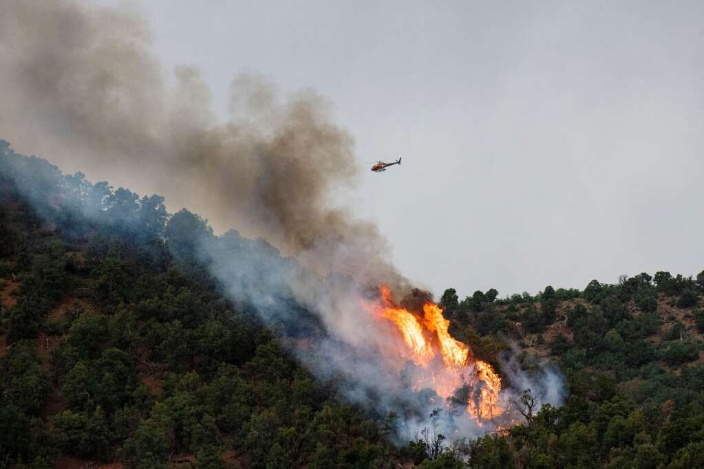 A helicopter flies over a burning wildfire that broke out on Friday evening from a lightning strike above Lower River Road in Old Snowmass on Friday, June 18, 2021. (Kelsey Brunner/The Aspen Times)