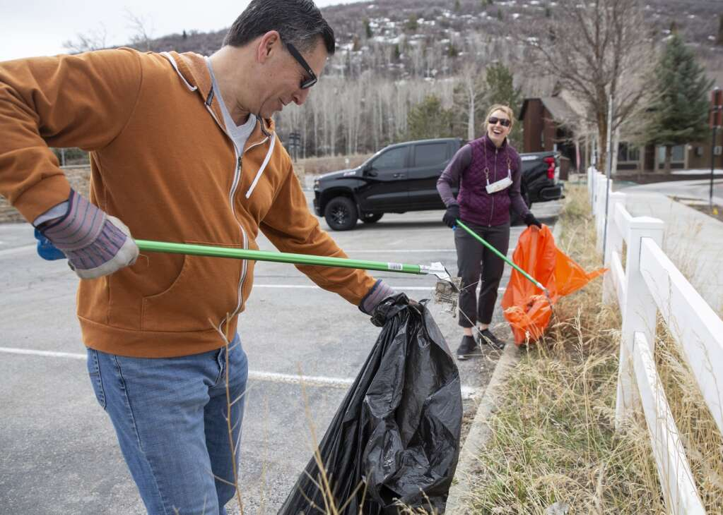 Andrew Cohen, left, and Jennifer Wesselhoff pick up trash near the Silver Mountain Sports Club and Spa in the Prospector neighborhood Saturday morning during an Earth Day cleanup effort organized by Recycle Utah. Cohen and Wesselhoff were one group of multiple that fanned out across the Rail Trail, Prospectorr neighborhood and near City Park to pick up litter. (Tanzi Propst/Park Record)