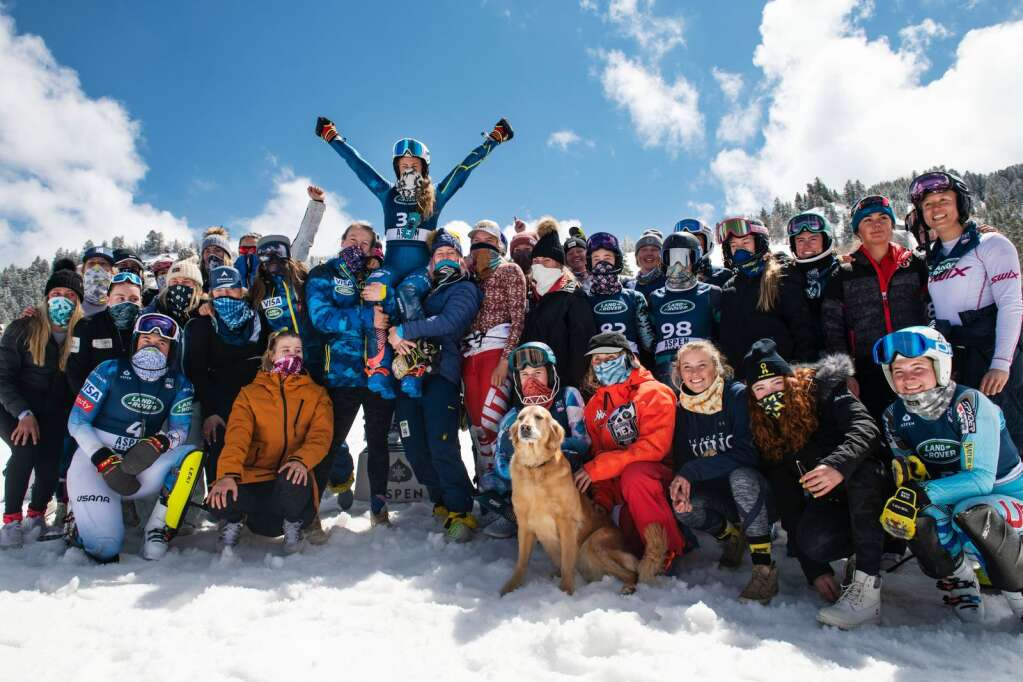 Women alpine skiers pose for a group photo while holding Resi Stiegler after the Women's Slalom National Championships at Aspen Highlands on Friday, April 16, 2021. (Kelsey Brunner/The Aspen Times)